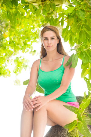 Blonde girl sitting on tropical tree