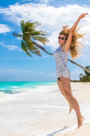 Jumping girl on the sandy beach 版權商用圖片