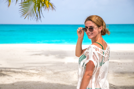 Young woman with sunglasses at the dream beach laughs at the camera