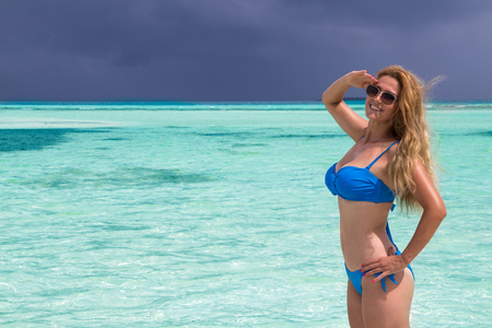 Blonde Girl in blue bikini in the turquoise sea Foto de archivo