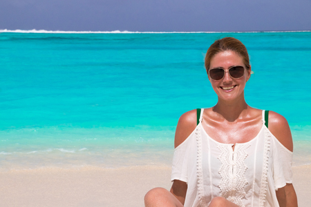 Beautiful woman in sunglasses tans at the dream beach Stok Fotoğraf