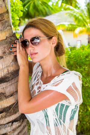 Young woman with sunglasses leans against a palm tree