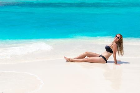Blonde Girl in black bikini on dream beach at the turquoise ocean 版權商用圖片