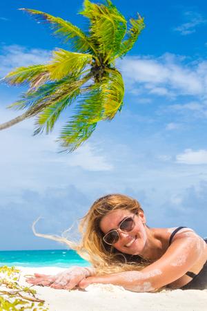 Happy girl in black bikini sunbathing on beach