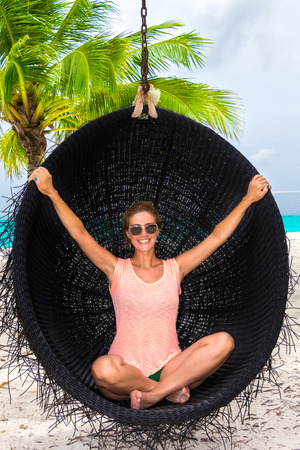 Beautiful woman relaxes on a swing on the dream beach