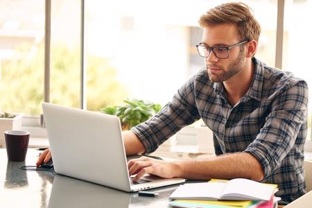 jovenes estudiantes: El hombre joven con gafas de trabajo en su portátil, con una taza de café agradable y temprano en la mañana, conseguir el negocio de la manera agradable y temprano en el día Foto de archivo