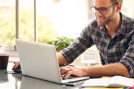 gente adulta: Feliz el hombre joven, con gafas y sonriente, mientras trabaja en su computadora portátil para obtener todo su negocio hecho temprano en la mañana con su taza de café