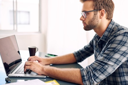 Horizontal image of a young businessman typing on his notebook while wearing a check shirt and glasses, with a cup of coffee within reach and paperwork just visible