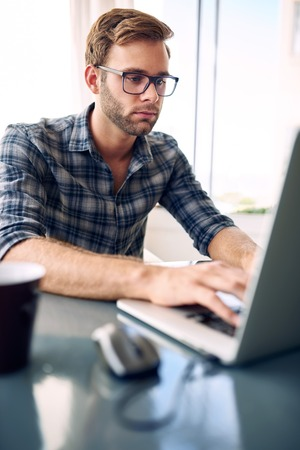 Portrait image of a young businessman typing on his laptop while wearing a check shirt and glasses, with a cup of coffee on the ready Reklamní fotografie