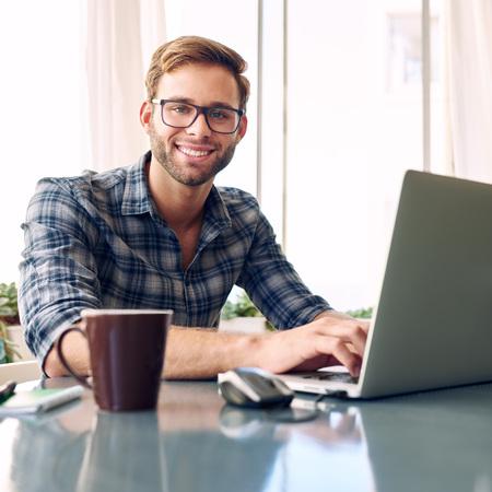 Jong, fris en levendig jonge student lachend naar de camera tijdens het werken aan een zakenman te worden op zijn nieuwe notebook