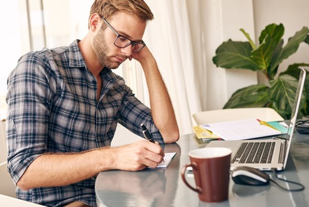 modern businessman: Young businessman with a trimmed beard and a check shirt sitting in his home office taking notes down from his laptops screen, with a cup of coffee waiting for him Stock Photo