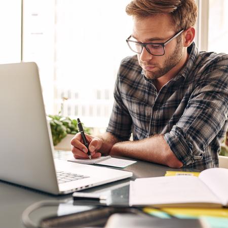 Studeert aan een zakenman te worden, terwijl het dragen van een bril en een geruit overhemd zittend achter zijn laptop bij zijn bureau