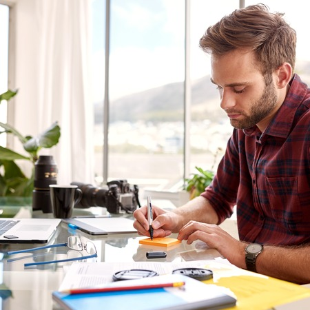 oficina desordenada: Ocupado hombre de negocios joven que toma notas en un bloc de notas, post-it, sentado en su escritorio de cristal en su oficina en casa con su caf� de la ma�ana Foto de archivo