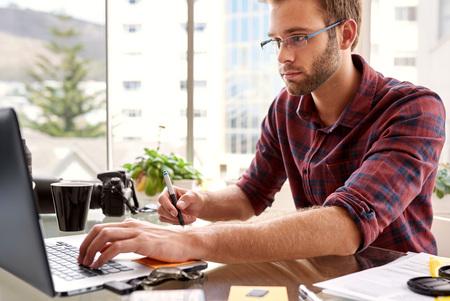 el fotógrafo profesional de imágenes jóvenes ocupados retoque en su ordenador portátil a partir de su estudio sobre la mesa de cristal mientras usa una camisa a cuadros marrón y gafas.