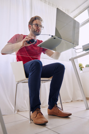 busy beard: Full body shot of a young student busy sorking on his laptop computer shot from below through his glass desk, while he works wearing a red shirt with a trimmed beard Stock Photo