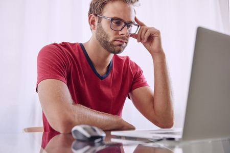 figure out: Young man staring at screen trying to figure out how he is going to overcome the problems that he has noticed Stock Photo