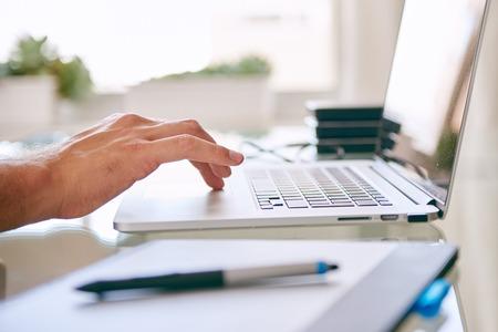 teclado: Primer plano de una mano en un cuaderno de desplazamiento, con copia espacio y una tableta digital en el primer plano y unidades de disco duro en el fondo