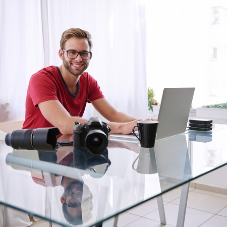 busy beard: Young professional photographer looking at the camera and smiling happily while working at his glass desk in his home office