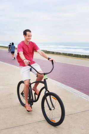 red shirt: A young teenage boy riding his bicycle on promenade next to the ocean, while wearing a red shirt.