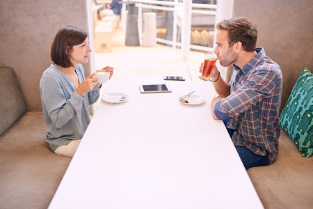 awkwardness: White man and woman having drinks together in a modern coffee shop. There is a tablet and a phone on the table between them, as well as a slight awkwardness amongst them Stock Photo