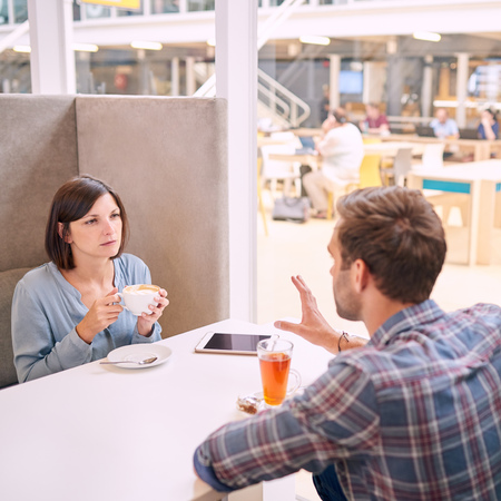 Woman looks angrily at her boyfriend as he tries to explain why it is that he will not be able to be home on her birhtday. Square over the shoulder shot of man using his hands to convey his message.