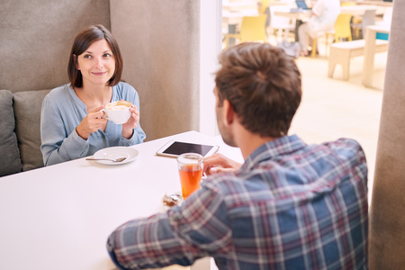 fails: Woman looks at someone out of the frame with a polite smile, while having a drink with her male partner whom is busy talking to her as she fails to show interest. Stock Photo