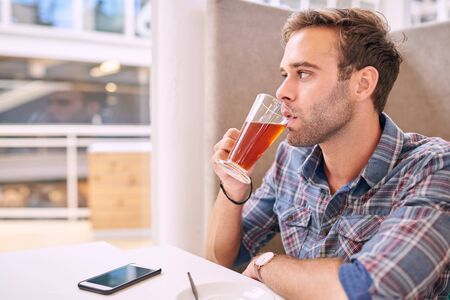 sip: casual caucasian male taking a sip of his red espresso and looking off camera into the copy space with his phone lyinjg on the table infront of him.