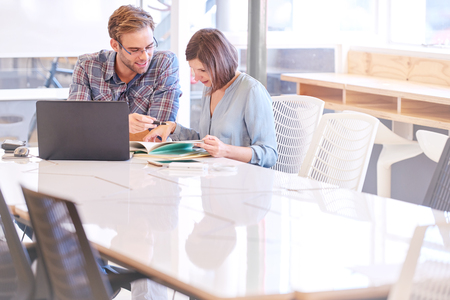 Businessman and businesswoman working together at the end of their new conference table in their new offices that they just opened together in their new business venture together. Stock Photo