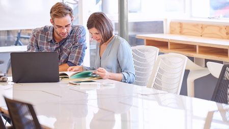 ensure: Businessman and businesswoman working side by side to ensure that their work together is done well without any glitches. Stock Photo