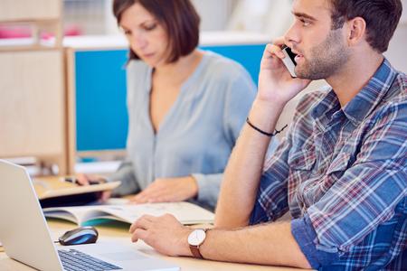 trabajando duro: El hombre cauc�sico que habla en su tel�fono con sus nuevos clientes potenciales mientras se est� sentado delante de su ordenador port�til con su socio de negocios mujer que trabaja duro en el fondo. Foto de archivo