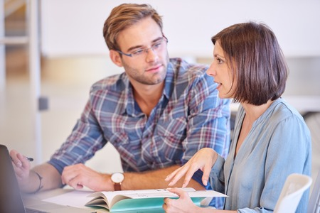 Female tutor busy explaining details to her male student as he tries to pay as much attention to her as possible, because he appreciates her mentorship