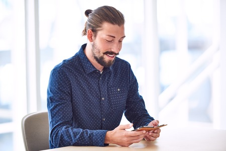 tied in: Trendy handsome man with long hair tied back in a bun busy using his mobile phone to stay connected while sitting at restaurant table.