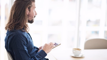 cappaccino: Caucasian man with long brown hair wearing a blue shirt using a tablet while seated at a table in a coffee shop next to large window allowing lots of natural light in.