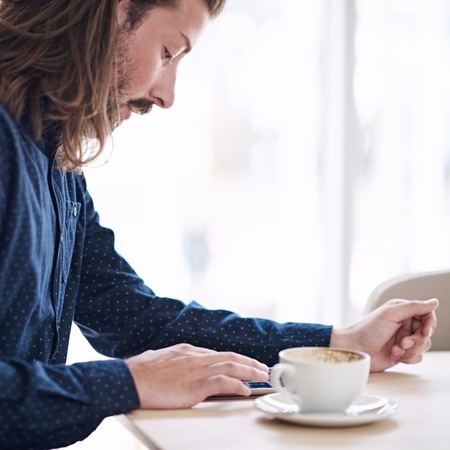 cappaccino: Square image of handsome caucasian man with long brown hair using tablet that is lying on the table in front of him next to his coffee.