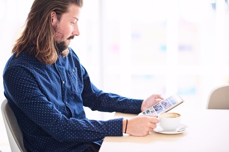 cappaccino: Young caucasian man sitting at a table next to a large window while holding a tablet in his hands and a cappaccino on the table in front of him.