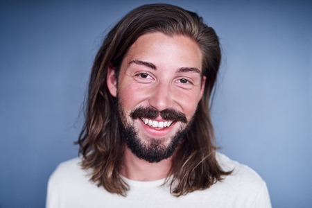 loose hair: Young white man with long loose brown hair and a beard standing in front of a blue background while wearing a white t-shirt with a positive aura.