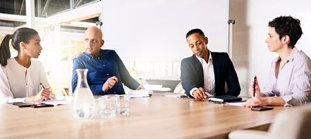 eclectic: collaberation between 4 racially diverse eclectic business executives on their new small business venture together as partners, taking place at a modern office at the end of a large conference table. Stock Photo