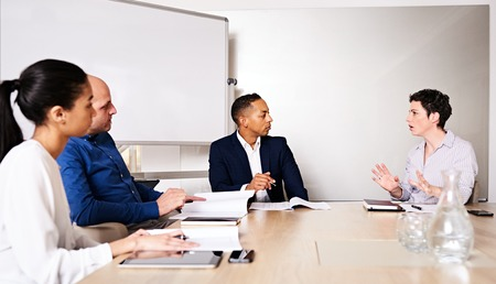 reasoning: four young diverse business partners conducting a meeting in the board room of their new offices at the new conference table, with the mature caucasian female busy explaing her reasoning