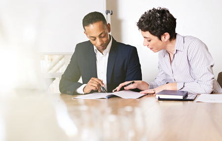 multi racial: Mature caucasian business woman paying close attention to the document being shown to her by her multi racial male business partner during their weekly meeting.