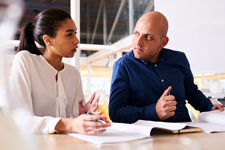 uncertainty: Young business woman expressing uncertainty about her caucasian male business partners new idea as he pays close attention to her reasoning Stock Photo