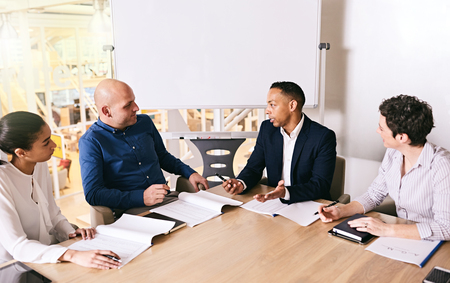 Business meeting between 4 unique individuals, both male and female, with a mixed race businessman busy speaking to the other educated individuals.