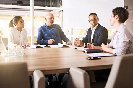 彼の成熟した女性のビジネス パートナー、シニア ビジネス partenr と重要な会議中に彼の側で個人的なアシスタントに耳を傾ける白人実業家。 写真素材