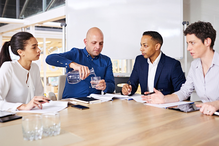 one on one meeting: Meeting between four successful entrepreneurs taking place while one of them pours himself a glass of water as the other business people continue to discuss the relevant topics to be decided on.