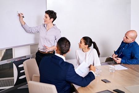 pitching: Mature intelligent businesswoman enthusiastic about starting her presentation about her new business idea that she is pitching to three potential investors of collaborators. Stock Photo
