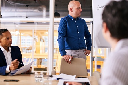 office presentation: Middle aged white man wearing a blue shirt busy giving a presentation to two potential investors in his latest business idea in his companys modern board room.