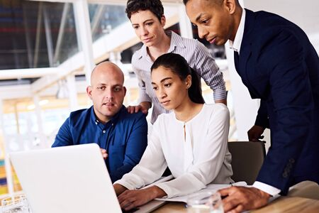 Group of young diverse and dynamic, well dressed architects busy looking over their latest rendering of the site in their major current project in which they are the core team. Stock Photo
