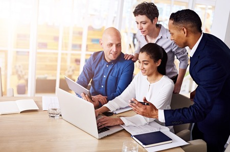 eclectic group of 4 entrepreneurs engaging in an online conversation via video conference using a laprop to discuss possible foreign production to save on labour costs. Stock Photo