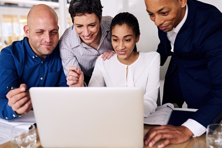 well dressed: tight image of four well dressed business executives looking at the same laptop screen with smiles on their faces, happy about the published partners bonus Stock Photo