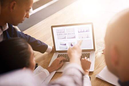 Group of four people pointing to and analysing graphs and charts all displayed on a notebook in front of them to determine performance goals for the next year as a group. Stock Photo