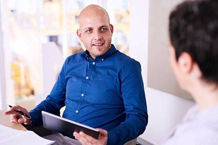 promising: Caucasian businessman holding electronic tablet while interviewing a female applicant whom looked like a promising candidate for the job on paper. Stock Photo